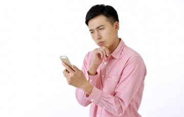 iPhoneを見て悩んでいる人